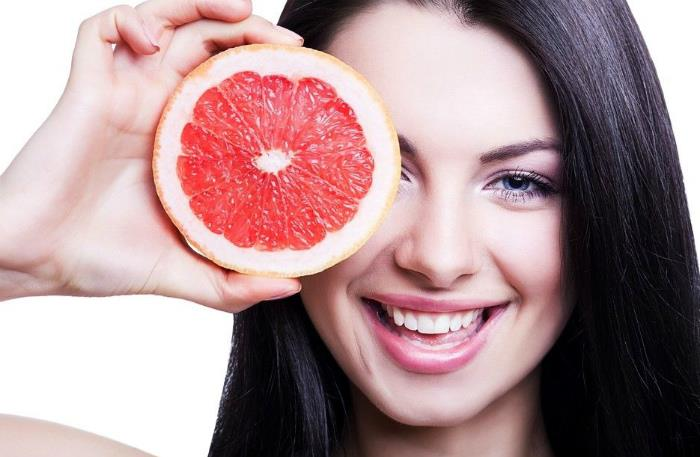 девушка со свежим грейпфрутом в руке